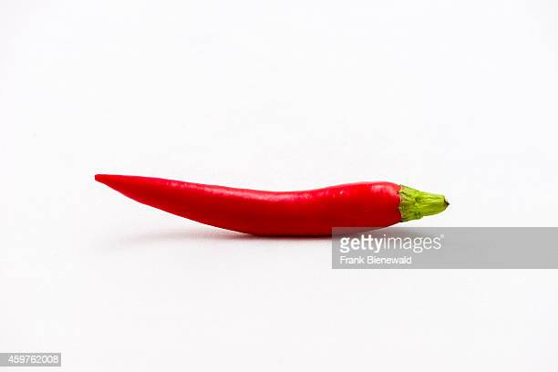 A red chili displayed on a white table