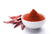Red Chilli Powder in a bowl with dried red chillies over colourful background or pile of red chilli powder over plain background