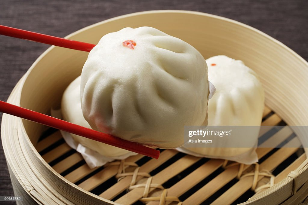 red chopstick holding dim sum (bao) : Stock Photo