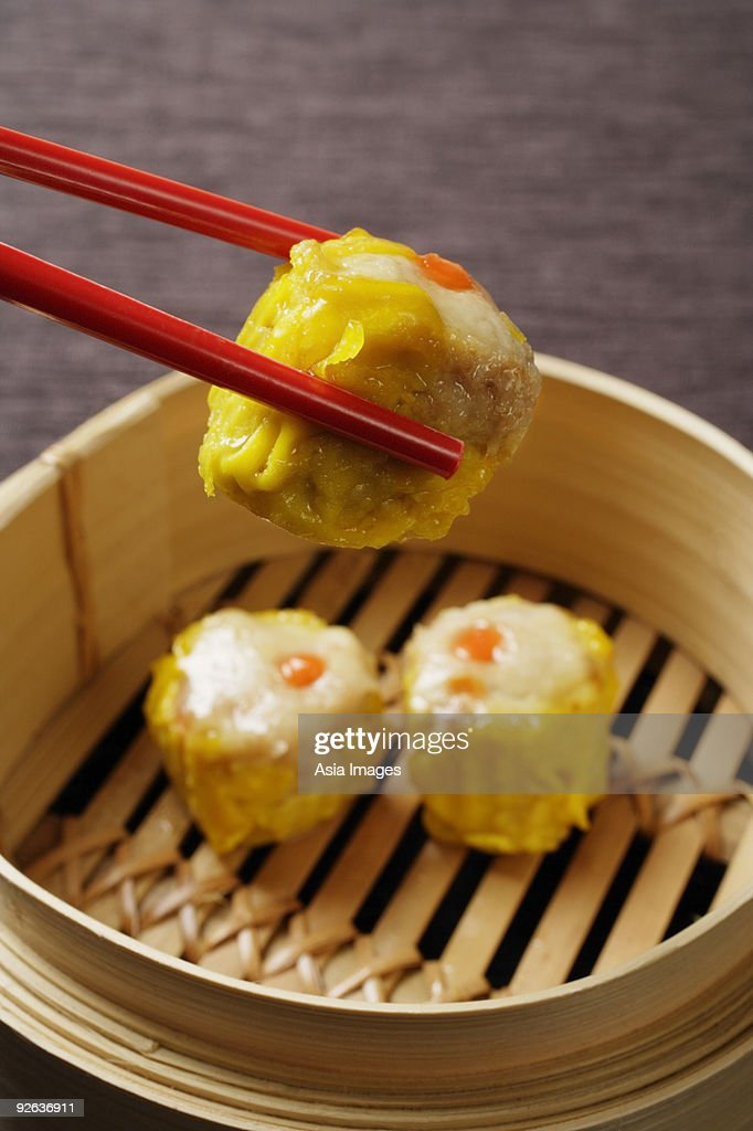 red chopsticks holding dim sum : Stock Photo