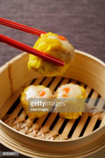 red chopsticks holding dim sum : Stock Photo