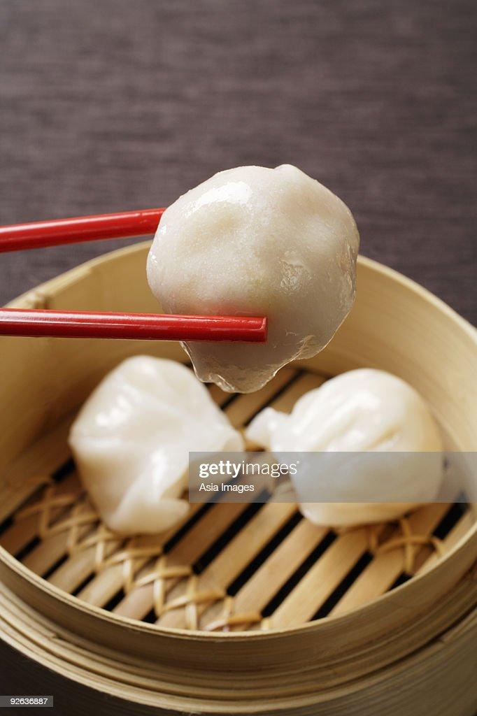 red chopsticks holding dimsum : Stock Photo