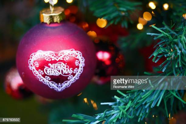 Red Christmas bauble with Christmas wishes hanging on tree