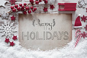 Paper With English Calligraphy Happy Holidays. Rustic White Christmas Flat Lay With Snow. Red Decoration Like Santa Hat, Sled, Snowflakes And Stars. White Wooden Background