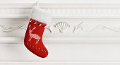 Red christmas stocking hanging on carved stone fireplace 3d rendering