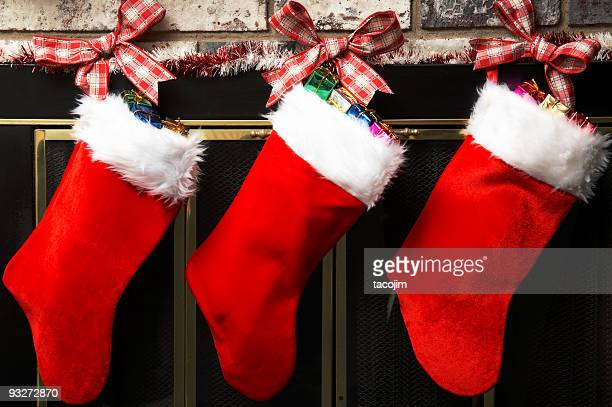 Red Christmas stockings hung up by tartan ribbon