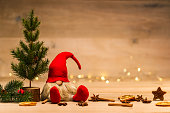 christmas dwarf sitting next to fir tree and x-mas decoration in front of bokeh lights