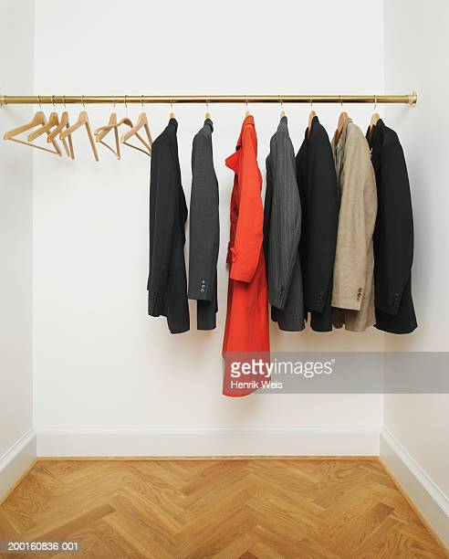 Red coat amongst suit jackets on hangers