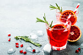 Red cocktail with blood orange and pomegranate. Refreshing summer drink on gray stone or concrete background. Holiday aperitif for Christmas party.