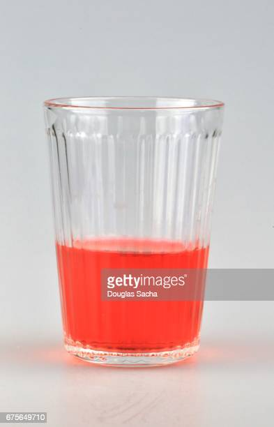 Red colored beverage in a clear serving glass