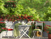 White furniture and red flowers оn the balcony