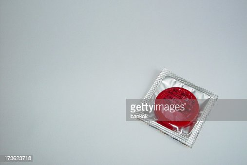 A red condom in a silver foil packet