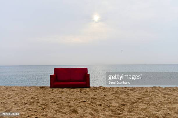 A red couch abandoned on the beach of Barceloneta