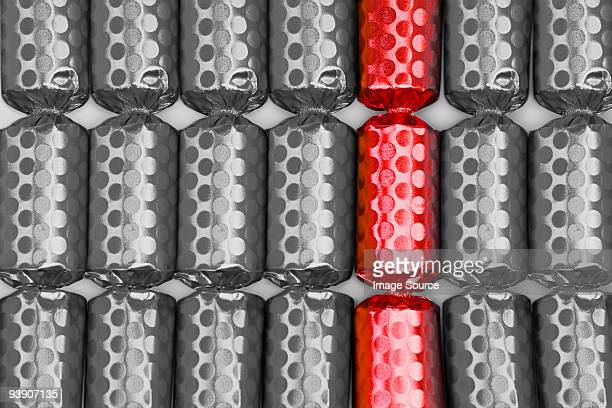 Red cracker amongst black and white