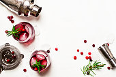 Red cranberry cocktail with ice, rosemary and vodka, bar tools, white background, top view