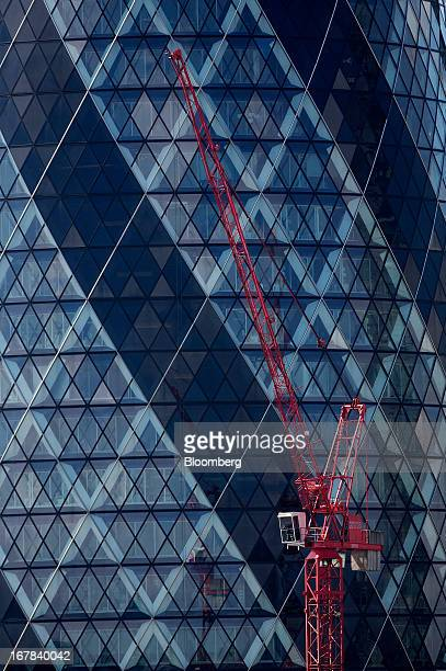 A red crane stands on a construction site in front of the Swiss Re building also known as 'the Gherkin' in central London UK on Tuesday April 30 2013...