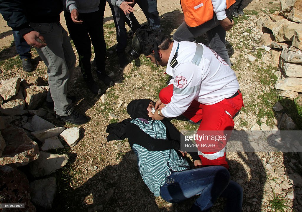 A Red Crescent paramedic attends to a Palestinian student after she inhaled tear gas fired by Israeli security forces during clashes in the village of Saair, east the West Bank city of Hebron, on February 24, 2013 following the death of a Palestinian prisoner held in Israel. Some 3,000 Palestinians held in Israeli jails were staging a one-day hunger strike in protest at the death of the inmate Arafat Jaradat, an official said, as security forces clashed with demonstrators in the West Bank. AFP PHOTO / HAZEM BADER
