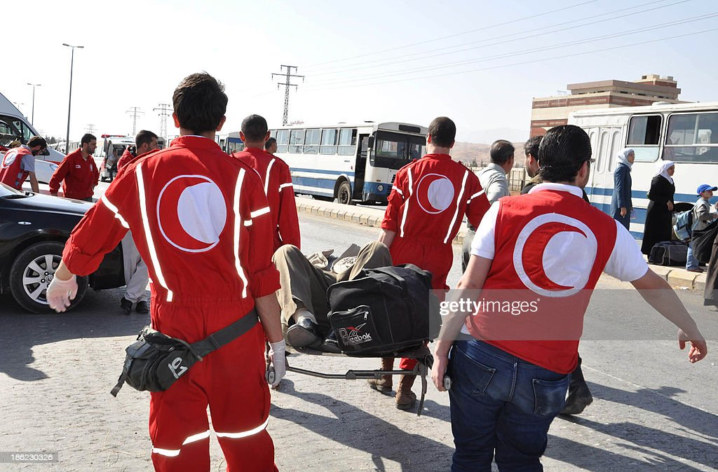 Red Cresent (the Muslim equivalent to the Red Cross) volunteers stretcher a man as Syrian civilians evacuate the war-battered suburb of Damascus, Moadamiyet al-Sham, with the help of the Social Affairs Ministry, as fighting between pro-government troops and rebel fighters continues in districts of the capital on October 29, 2013.