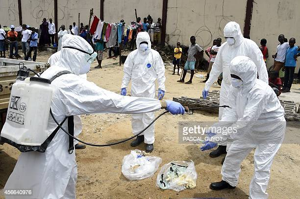 Red Cress personnel are sprayed with disinfectant after recovering a body of a person suspected of dying from the Ebola virus from his home in the...