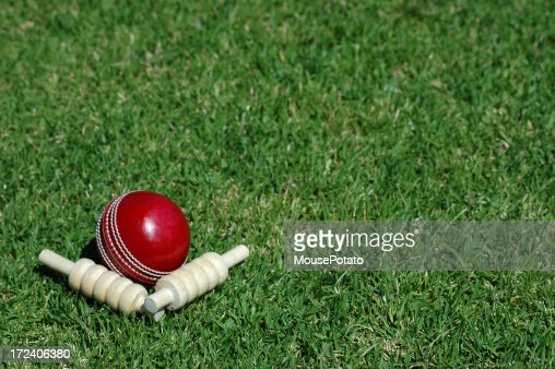 Red cricket ball and bails