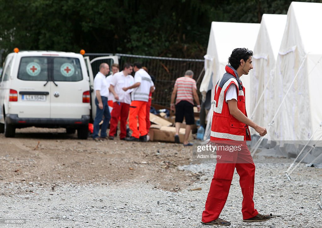 Red Cross employees work in a temporary refugee camp on July 25 2015 in Dresden Germany Several people were injured as around 200 German rightwing...