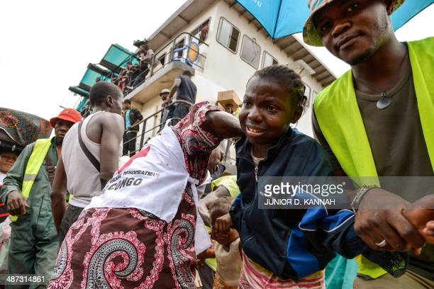 A Red Cross medical aid worker assists a young child arriving alongside other people from the Democratic Republic of Congo on an ATC boat from...