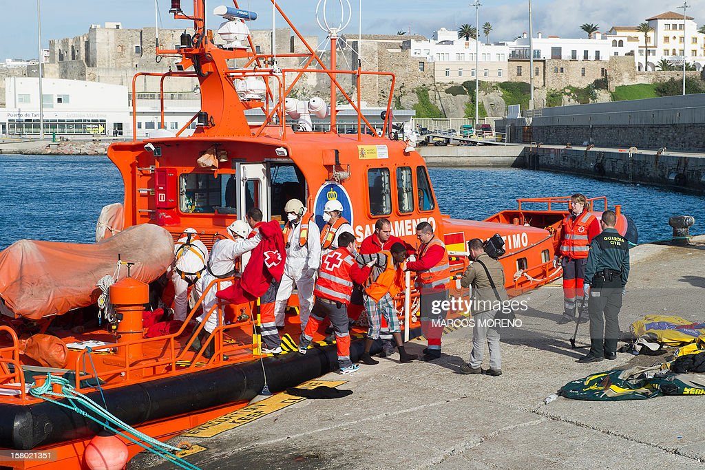 Red Cross members assist a would-be immigrant upon his arrival at Tarifa's harbour, on December 9, 2012 after being rescued off the Spanish coast by a boat of the Spanish emergency services. Attempts to reach Spanish soil by boat have increased over the last few weeks, as migrants try to make the most of the last remaining days of warm weather. AFP PHOTO / MARCOS MORENO