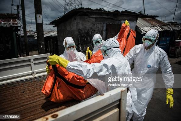 Red Cross members carry dead body of Mambodou Aliyu died due to the Ebola virus in Monrovia Liberia on 15 October 2014