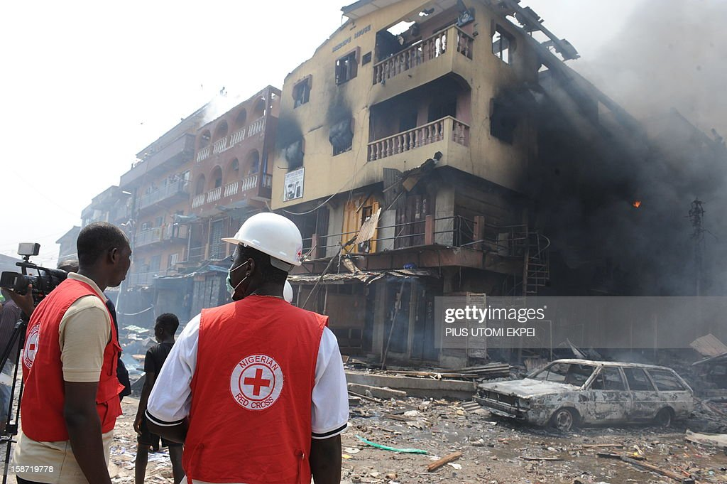 Red Cross officials walk look at a building on fire after a heavy explosion on December 26, 2012 in Lagos. Fire ripped through a crowded neighbourhood in Nigeria's largest city and wounded at least 30 people after a huge explosion rocked a building believed to be storing fireworks, officials said. Fireworks continued to explode well after the fire began while smoke was heavy and the blaze intense, making it difficult for rescue workers and firefighters to approach the scene.