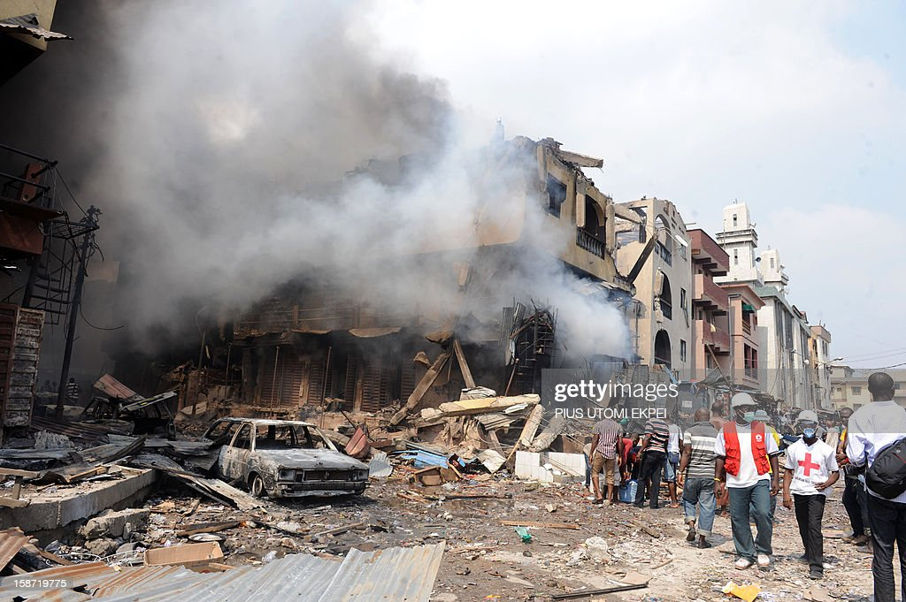 Red Cross officials walk past a building on fire after a heavy explosion on December 26, 2012 in Lagos. Fire ripped through a crowded neighbourhood in Nigeria's largest city and wounded at least 30 people after a huge explosion rocked a building believed to be storing fireworks, officials said. Fireworks continued to explode well after the fire began while smoke was heavy and the blaze intense, making it difficult for rescue workers and firefighters to approach the scene.