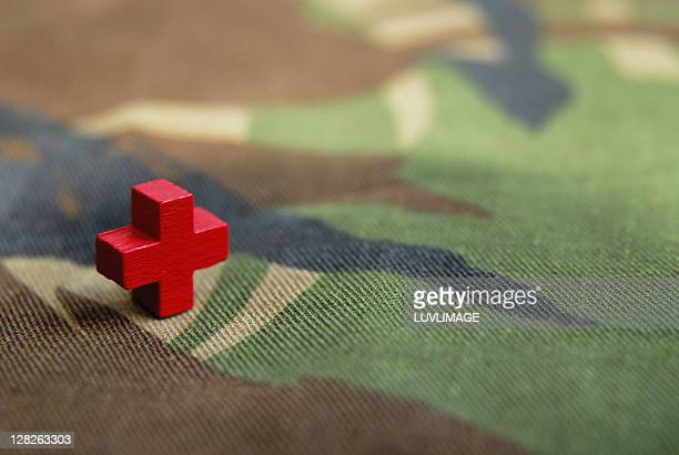 Red cross on a camouflage background