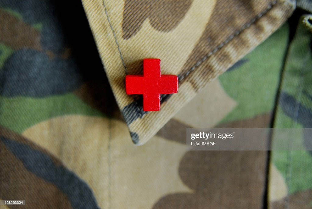Red cross on the collar of a camouflage jacket : Stock Photo