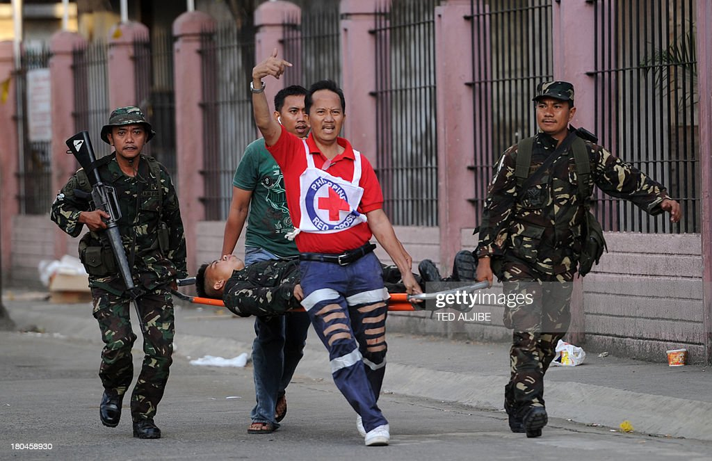 A red cross personnel shouts for an ambulance as he and soldiers carry a wounded soldier after a mortar shell fell nearby while Philippine troops...