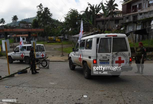 Red cross vehicles carrying evacuees speed past a military check point in Marawi in southern island of Mindanao on May 27 2017 The Philippine...