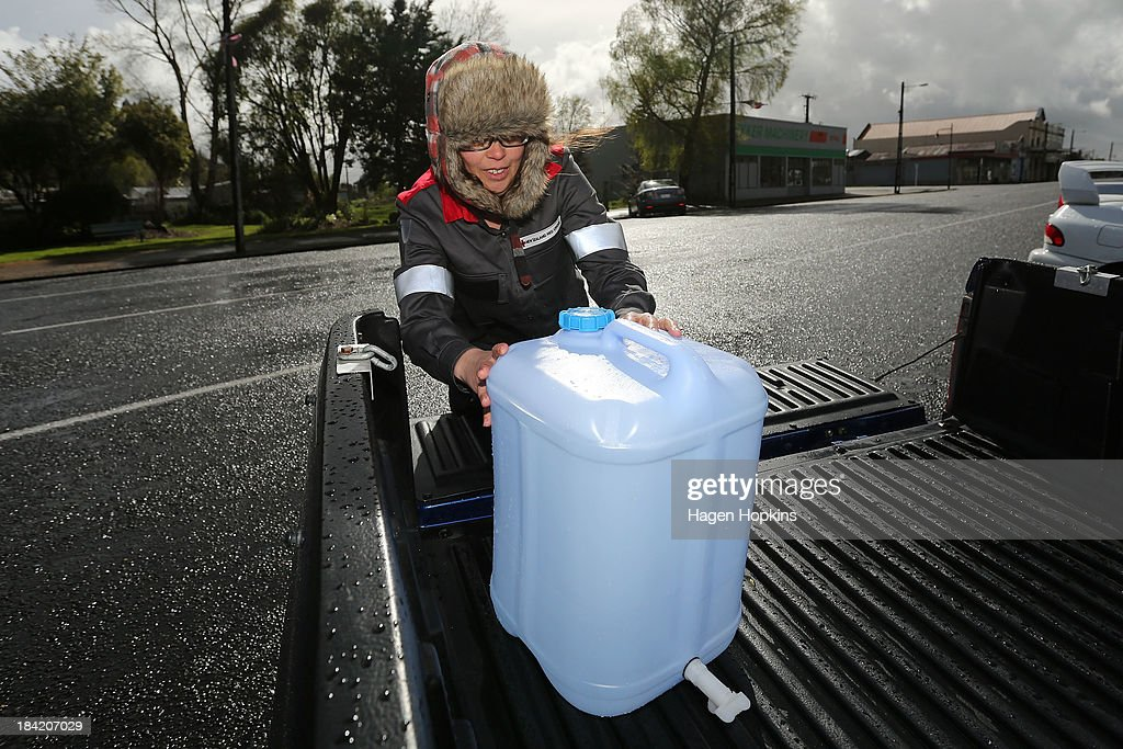 Red Cross volunteer Gypsy Anderson places a container of fresh water onto the tray of a local resident's ute on October 12, 2013 in Raetihi, New Zealand. Work has begun to flush a stream contaminated by a large diesel spill at Tongariro National Park. A tank from the Turoa Ski Field has leaked 15,000 litres of diesel into the Makotuku stream.