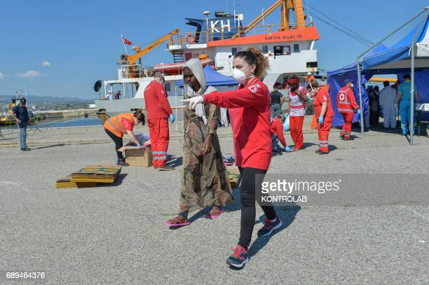 A red cross volunteer helps a girl during the landing of migrants by Turkish cargo ship Kaptan Hilmi III in port of Corigliano Calabria southern...