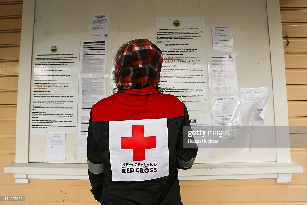 A Red Cross volunteer reads a notice board displaying information on the water contamination on October 12, 2013 in Raetihi, New Zealand. Work has begun to flush a stream contaminated by a large diesel spill at Tongariro National Park. A tank from the Turoa Ski Field has leaked 15,000 litres of diesel into the Makotuku stream.