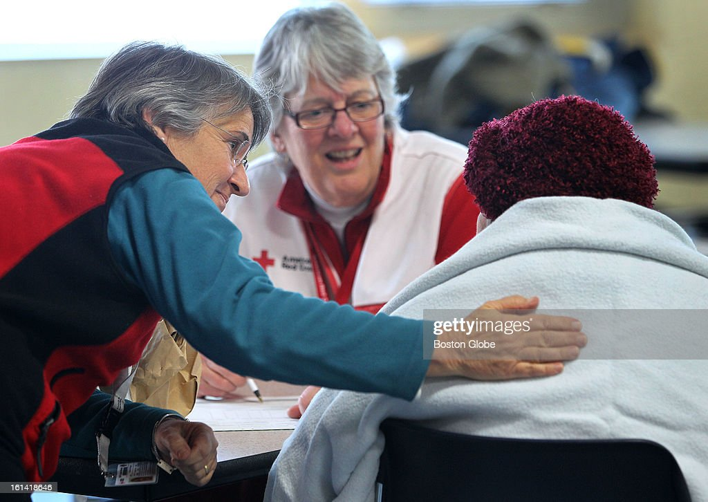 Red Cross volunteers Bobi Steingart, left, and Mary Elkins speak to a client during the intake interview. A shelter at Weymouth High School, to house those affected by the blizzard, was originally opened by the town, which requested the Red Cross to take over. All volunteers are from Springfield, Mass. The shelter is still accepting clients, on Sunday, February 10, 2013.