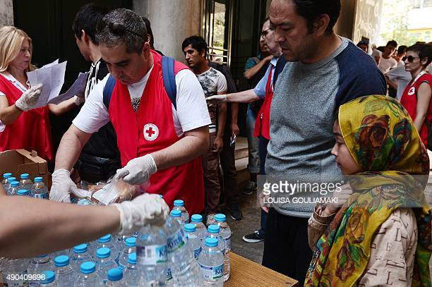 Red Cross volunteers distribute water and sandwiches to migrants temporary stranded in Athens at their premises in center of Athens on September 28...