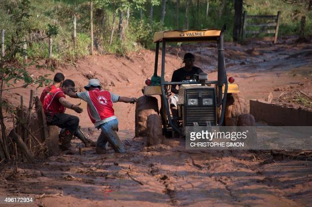 Red Cross volunteers try to cross a muddy area of Gesterio part of the Barra Longo city 60 km from Mariana Brazil on November 07 2015 Rescuers...