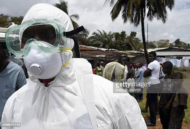 A Red Cross worker makes his way to collect a body of a person suspected of dying from the Ebola virus from a house in the Center Street neighborhood...