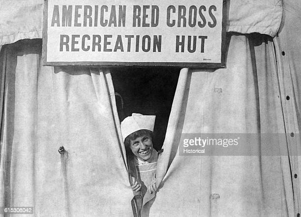 A Red Cross worker smiles out from behind a curtained doorway when it's time to open the American Red Cross recreation hut at American Military...