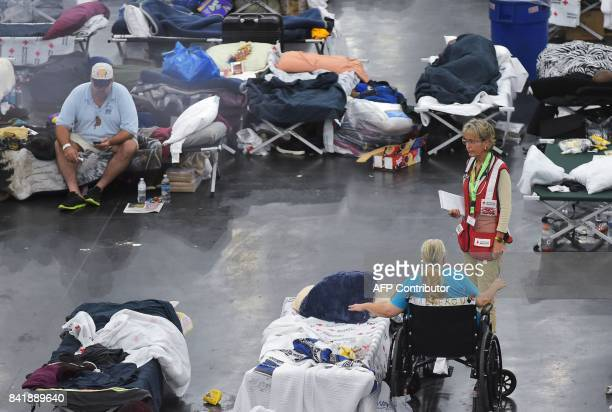 A Red Cross worker talks to a woman inside of the George R Brown Convention Center which has been a shelter for evacuees from Hurricane Harvey in...