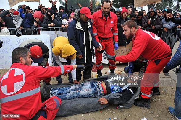 Red Cross workers assist a man who fainted as he was waiting along with other migrants and refugees to cross the GreekMacedonian border near the...