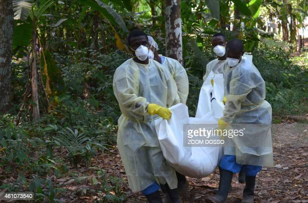 Red cross workers wearing masks carry the body of a person who died from Ebola during a burial with relatives of the victims of the virus in Monrovia...