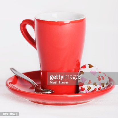 Red cup and saucer with love heart chocolate, against white background : Stock Photo