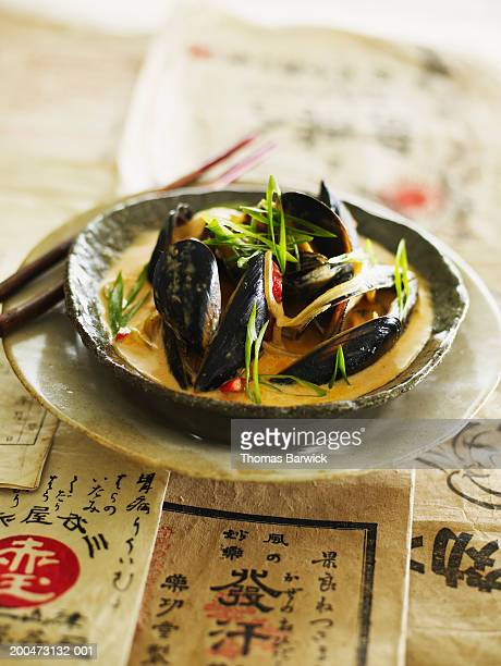 Red curry mussels with cilantro and spring onions, elevated view