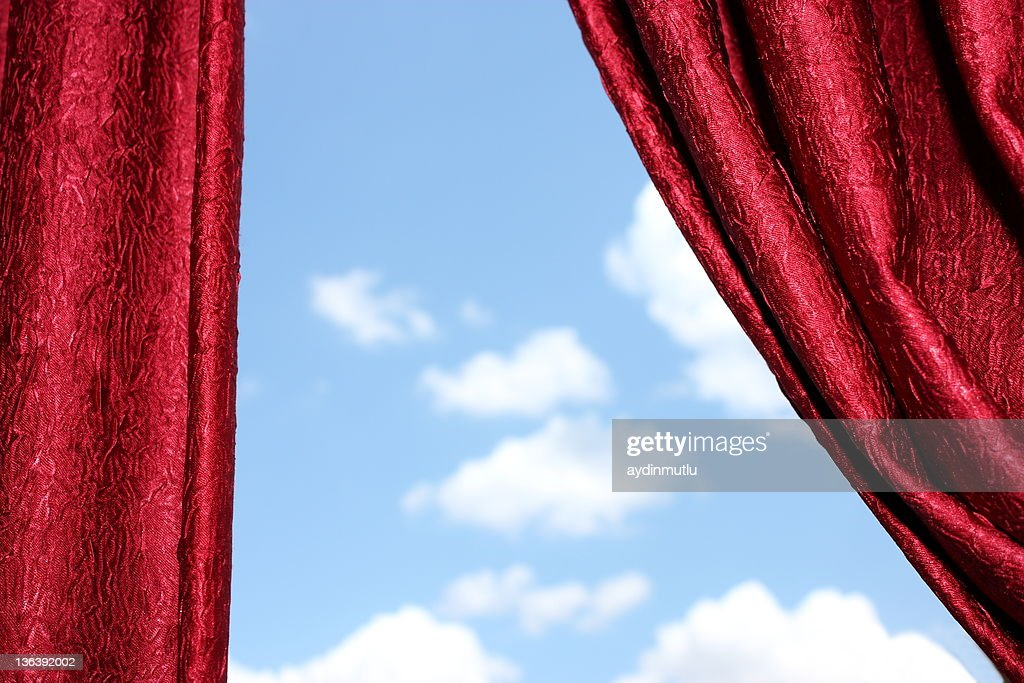 Red curtains and cloudy sky