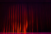 Red velvet curtains with the lights of the show and the wood flooring parquet.