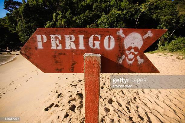 Red danger sign on beach